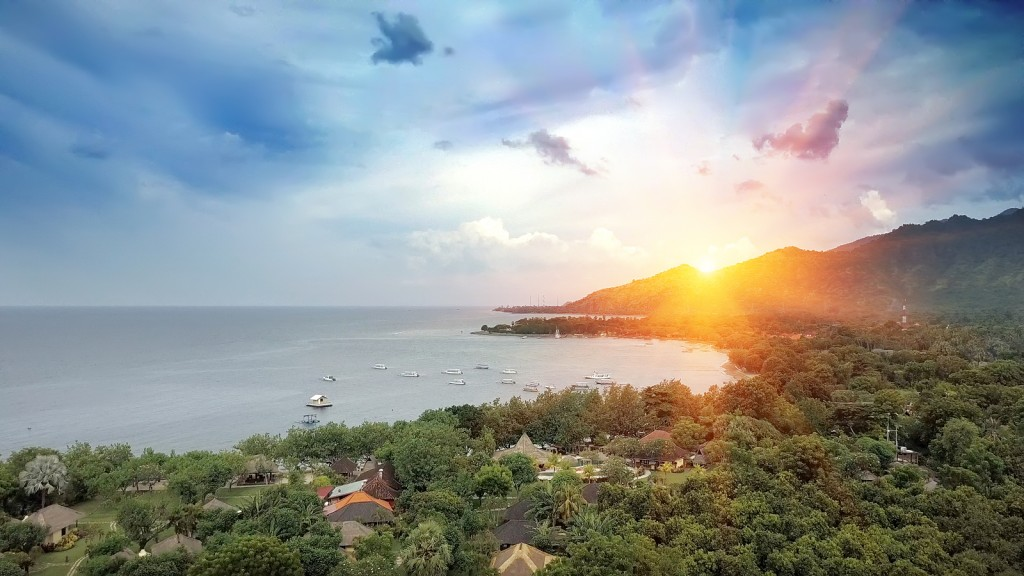 The North of Bali - Pemuteran. Aerial view from drone. Palm trees on an ocean coast and green hill